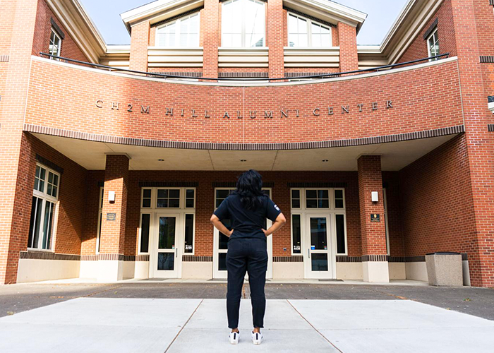 Photo of student standing in front of the alumni center and looking up at the building name