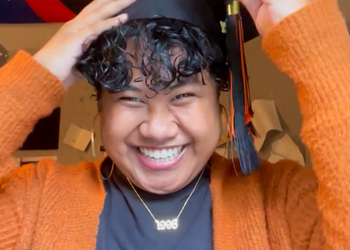 Screenshot of student smiling and placing grad cap on their head in video