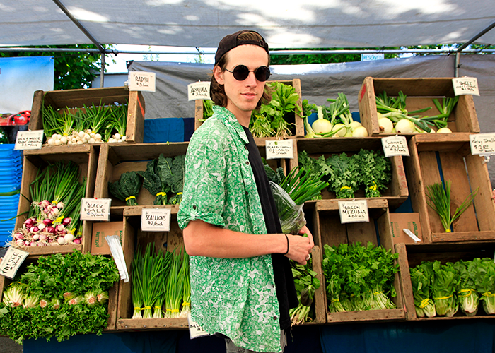 Person smiling at the camera holding leeks while shopping at the Corvallis Farmer's Market