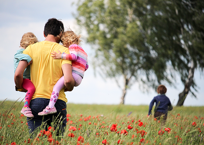 Photo of father carrying two young children through a poppy field while another child runs ahead