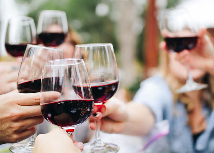 Photo of several hands clinking red wine glases together