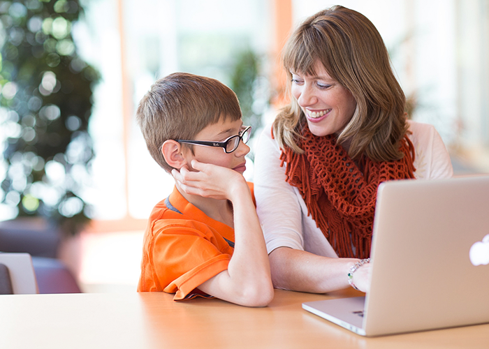 Mother using a laptop at a table and smiling at her child sitting next to her