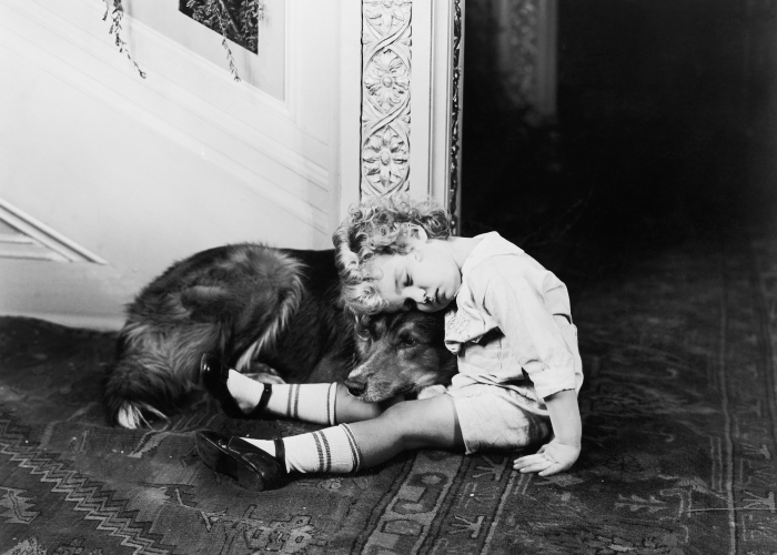 Black and white photo of a child sitting on the floor and leaning on a golden retriever