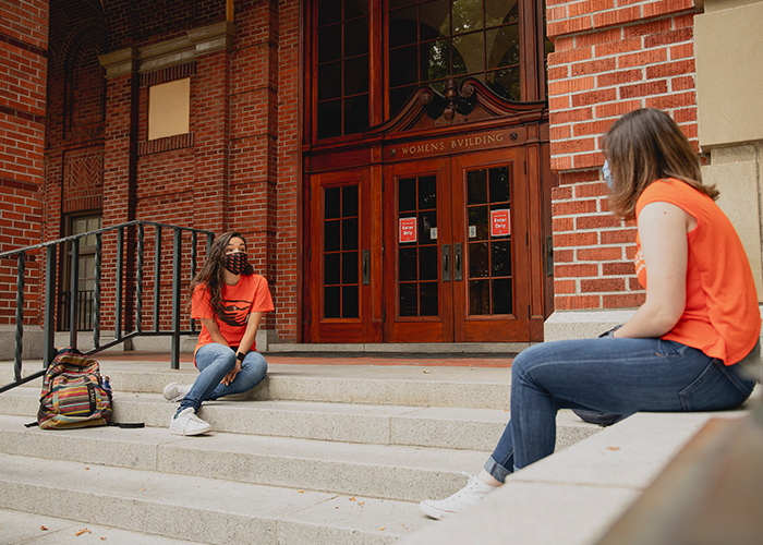 Photo of two students sitting in front of the Women's Building using masks and social distacing to hang out