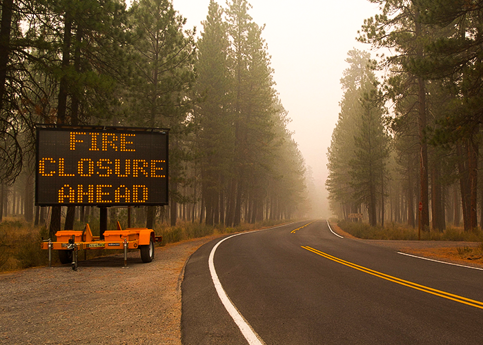 """Photo of road without traffic with sign that reads """"fire closure ahead"""" and smoke in th air"""