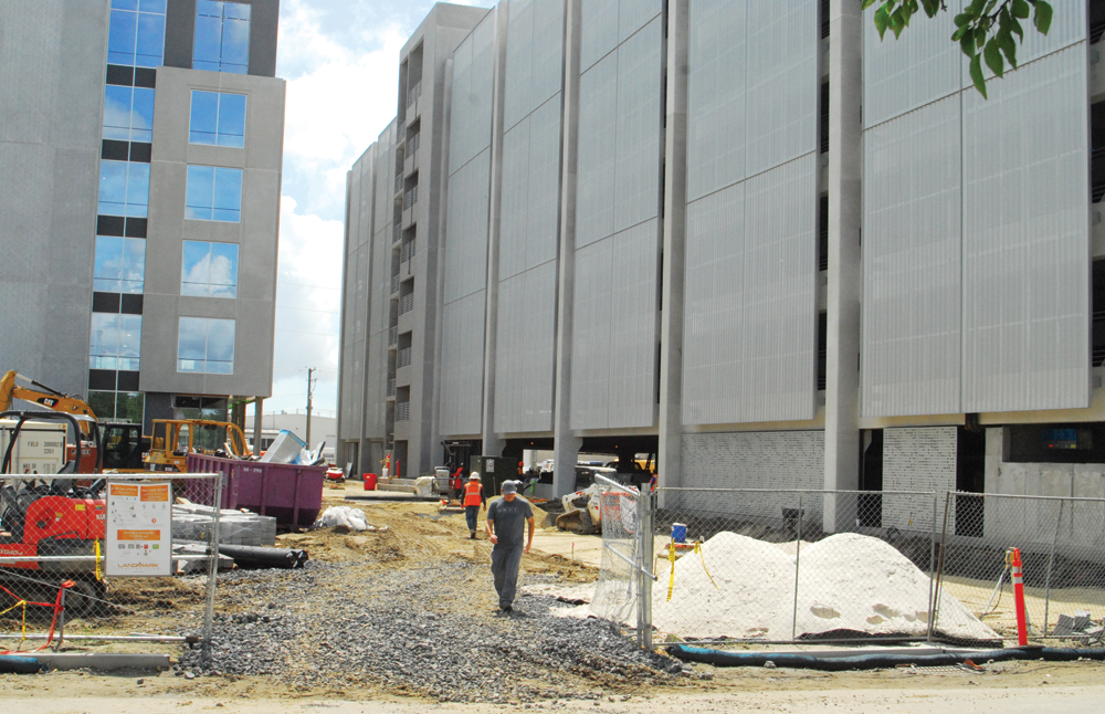 Photo shows a construction site with a chain link fence around it. A gray building with multiple windows is being built at left and a gray building with fewer apparent windows is being built at right. Workers are walking through the site, which has gravel, a dirt pile, construction equipment and a purple trash bin.