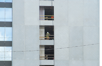Image shows a gray building with three windows at the left and three open areas in the middle. A man in construction gear is in the middle opening.